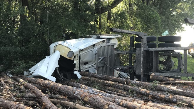 A log truck lies on its side Wednesday morning following a crash north of Dunnellon in which the driver was seriously injured.