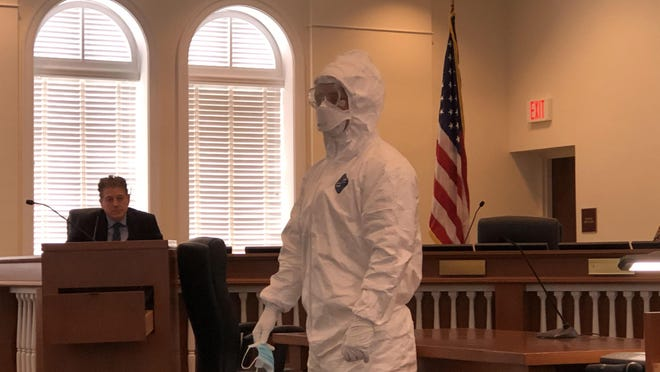 An EMS staffer demonstrates the protective gear used by hospital workers and first responders when treating a coronavirus patient during a Public Safety Committee meeting on March 9.