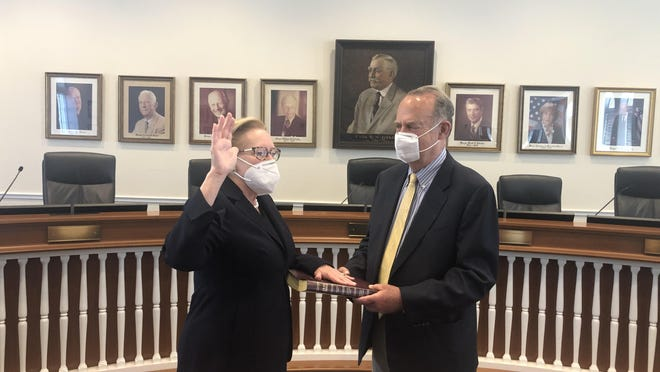 Margaret Zeidman, joined by husband Mark Zeidman, is sworn to a third term on the Town Council Tuesday in the meeting chambers at Town Hall.