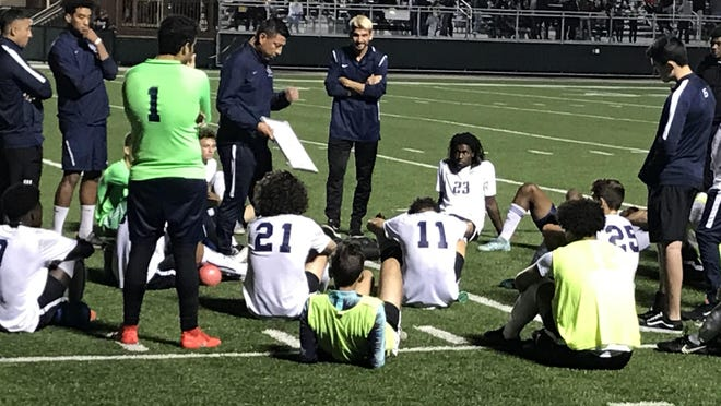 American Heritage boys soccer coach Jonathan Frias, holding clipboard, talks to his team. The Stallions lost 6-0 to University School in Saturday's Class 3A state semifinals.
