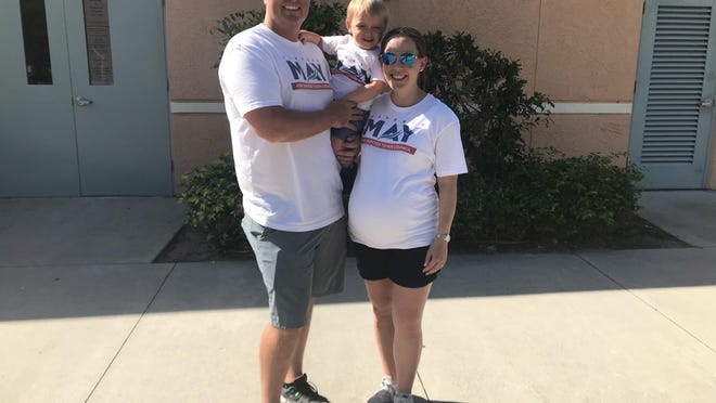 Cameron May stands outside the polling location at Independence Middle School on Tuesday with wife Magen and son Merrick.