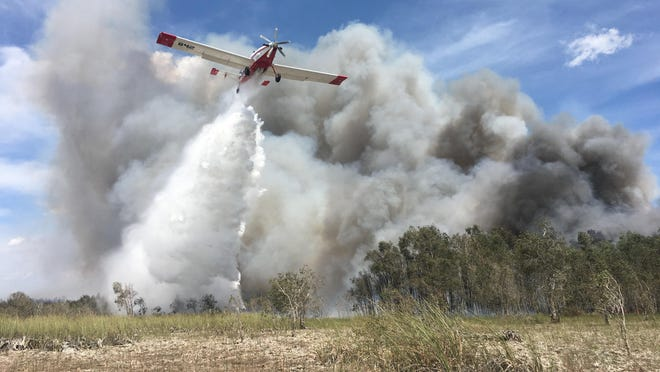 A Single Engine Airtanker (SEAT) drops water on the hottest spots of the Sunday Afternoon Fire in Everglades National Park on April 23, 2020.