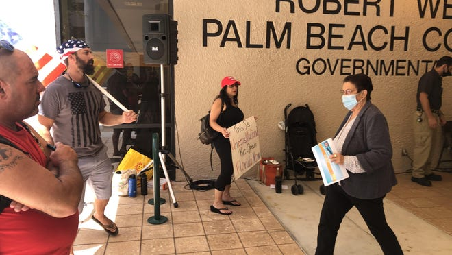 Dr. Alina Alonso, Palm Beach County health director for the state health department, walks past protesters seeking a faster reopening of Palm Beach County Tuesday outside a county commission meeting.