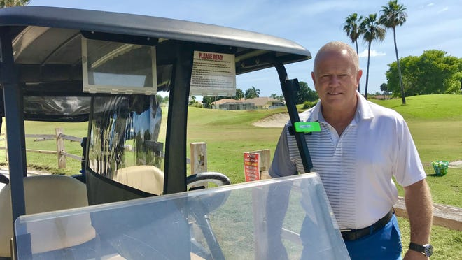Brian Symonds, owner of Winston Trails Golf Club in Lake Worth, stands next to a golf cart with one of his Golf Safer Protection Shields installed.