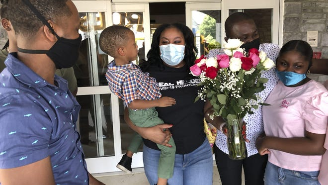 Teisha Roberts, center, a nursing director, is greeted by her family as she prepares to leave Park Springs elder care facility in Stone Mountain, Ga., Saturday, June 13, 2020. Workers who agreed to live at Park Springs to keep its residents safe from the coronavirus are back with their loved ones for the first time in nearly three months.