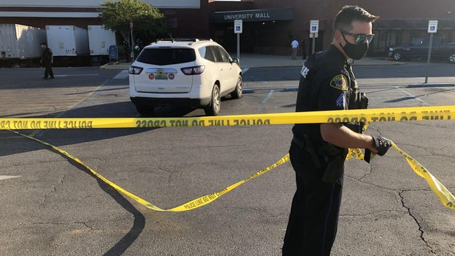 Tuscaloosa police officers take down crime scene tape outside of University Mall Saturday evening. Around 5 p.m., officers were called out to University Mall after a shooting. Two were injured.