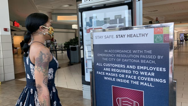 A shopper stands next a coronavirus safety sign posted at one of the entrances to Volusia Mall in Daytona Beach on Saturday, July 11, 2020.