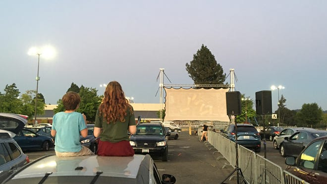 Two kids have a rooftop seat for Lane Event Center's Midway Movies on Friday.