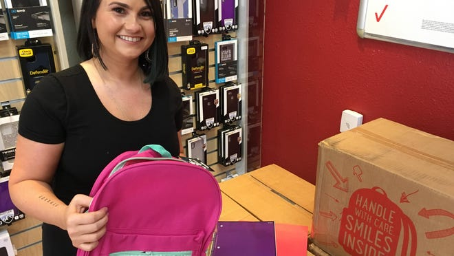 Danielle Mears, manager at Wireless Zone of Ocala, holds one of the backpacks will be filled with school supplies and given to school-age students on Sunday.