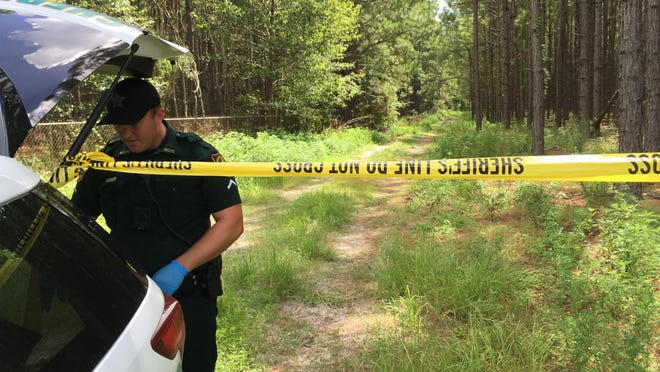 Marion County Sheriff's Office Deputy R. Artman secures the path to the scene of single-engine aircraft crash Sunday morning near the Marion County Airport in Dunnellon. The crash claimed the life of the pilot and sole occupant of the aircraft.