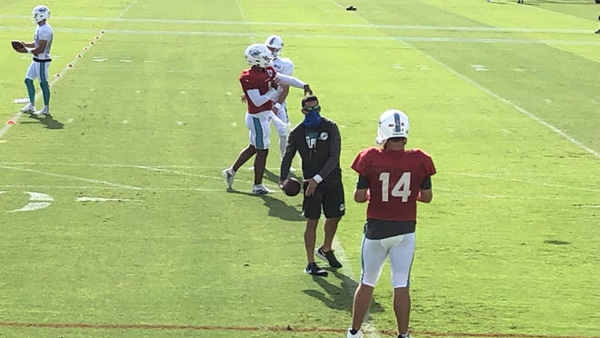 Miami Dolphins quarterback Tua Tagovailoa (1) talks with a coach with Miami Dolphins quarterback Josh Rosen (3) at Miami Dolphins training camp August 17, 2020.