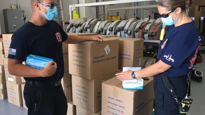 St. Augustine firefighters Ryan Costeira and Sherry Walker look at masks ordered by the city of St. Augustine to help businesses with operating during the COVID-19 threat. The City of St. Augustine Beach is considering a similar program.