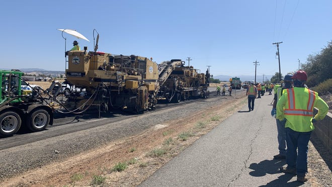 """The """"recycling train'' scoops up the old asphalt, grinds it, blends it with a binder and lays it down to form the new pavement. [COURESTY OF TECHNISOIL_"""