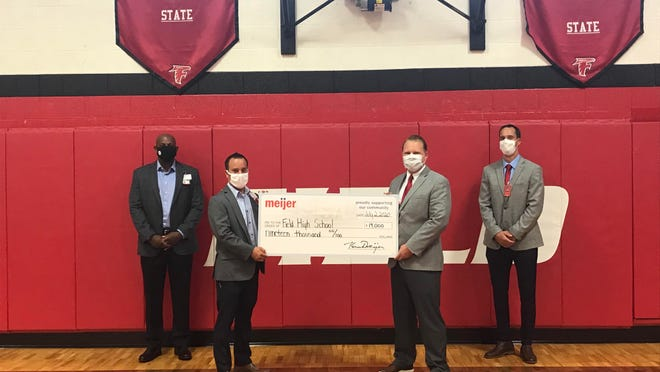Meijer representatives present Field representatives with a check to fund new scoreboards for the Falcons' gymnasium.