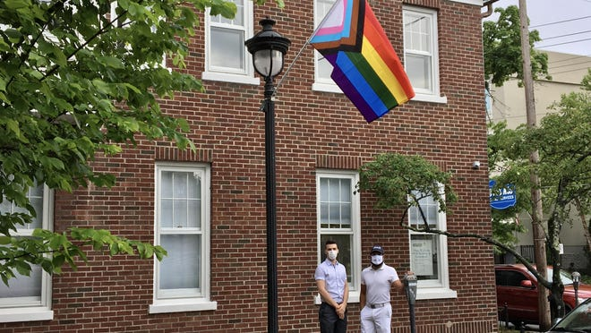 "Benny Vukaj and Michael Moreno stand outside Novus ACS Medical Services in Stroudsburg with a ""Progress PRIDE"" flag on Wednesday afternoon. The PRIDE Flag initiative, launched by the Pocono Chamber of Commerce's LGBTQ+ Business Council in 2019, has expanded this year, with about 110 flags decorating Stroudsburg and Mount Pocono."