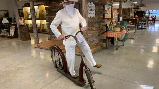 """All alone beside the replica of his l809 pioneer cabin inside Walnut Creek's German Culture Museum, Jonas """"Der Weiss"""" Stutzman, the 232-year-old """"Father Of Amish Country"""" is portrayed trying to balance on an antique """"Ingo"""" bicycle (often called a """"clown bike"""".) The pioneer, who was Amish but dressed in white (weiss), thus marked the 10th anniversary, Aug. 14, of the museum's move into a new and expanded showroom in the Walnut Creek Library building. Although wearing a mask, Der Weiss said COVID-19 pandemic concerns prompted museum board members to hold off reopening for public tours until 2021."""