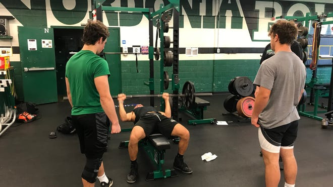 Nordonia junior Cooper Rusk uses the bench press as Billy Levak (left) and Sal Perrine (right) spot him. Scenes like this are returning to local high schools as the OHSAA allows skill workout to return.