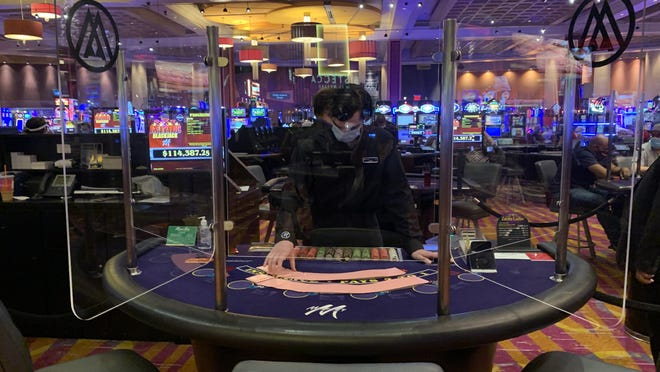A table dealer at Mount Airy Casino Resort in Mount Pocono wears a mask and is separated from players by a plastic partition. Casinos across Pennsyvlania have enacted similar stands in front of a partition set up as one of the new safety protocols.