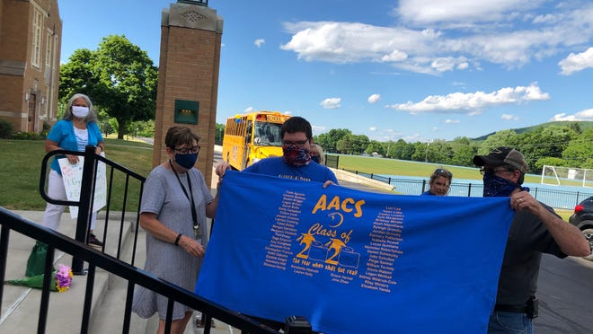 Alfred-Almond secondary principal Susan Bain-Lucey accepts a banner from the Class of 2020 in honor of her retirement. The banner featured class members' names and an acknowledgment of the COVID-19 crisis that made this school year memorable.