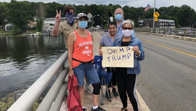Local residents display their opposition to President Donald Trump on the River Styx bridge over Lake Hopatcong Saturday, June 27. A boat parade in support of the president was postponed due to weather, though some demonstrators still came to the bridge for a brief time.