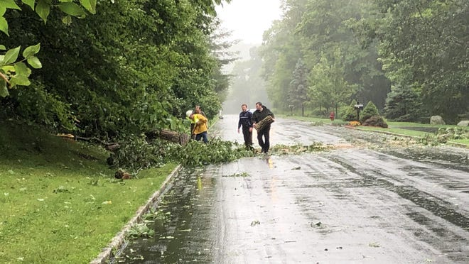 A crew works to clear a fallen tree across Waters Edge Drive in Sparta Tuesday, Aug. 4.