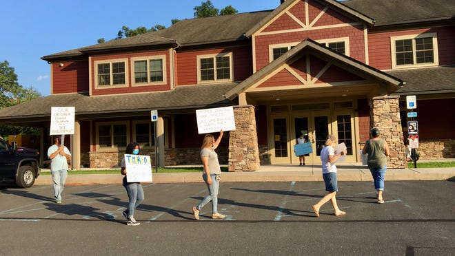 A small group of protesters gathered outside the Smithfield Township building on Tuesday before a hearing on a zoning amendment that would allow a rehab center to open on a golf course.