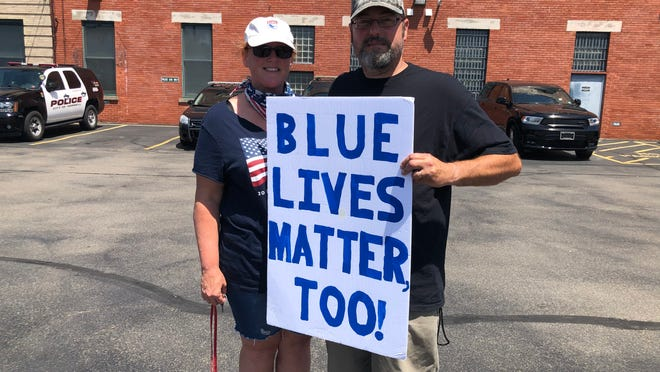 """Amy and Gary Mikolajczyk hold up a """"Blue Lives Matter Too"""" sign outside the Hornell Police Department Saturday following a Blue Lives Matter rally in the city. Organized by Amy Mikolajczyk and Dave Prete, the rally drew over 50 people to the event in support of the Hornell men and women in blue as well as law enforcement personnel across the country. Rally goers, carrying signs and voicing support for police, met at the police station and later gathered at the lawn area across from Hornell City Hall. According to its mission statement, the goal of Blue Lives Matter is to honor and recognize the actions of law enforcement and to strengthen public support for police."""
