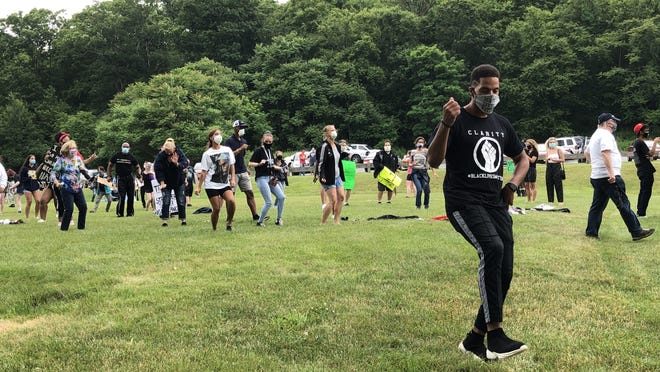Newton resident Scott Paul, foreground, leads a dance routine among attendees at the Black Lives Matter Byram rally at CO Johnson Park Saturday, June 27.