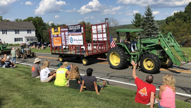 Spectators wave at tractors passing in front of the Sandyston Municipal Building during the township's annual Tractor Parade Saturday, Aug. 22.