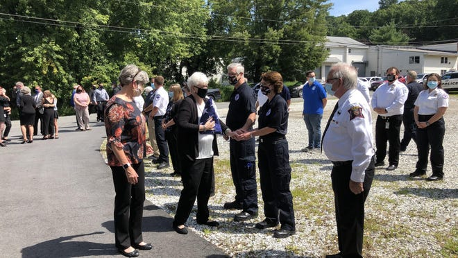 Pat Sabourin, second from left, guided by her daughter, Pat Casteel, shakes hands with local first responders during a final radio call ceremony for her husband George at the Ogdensburg First Aid Squad building on Willis Avenue on Friday. George Sabourin died Monday at age 84.