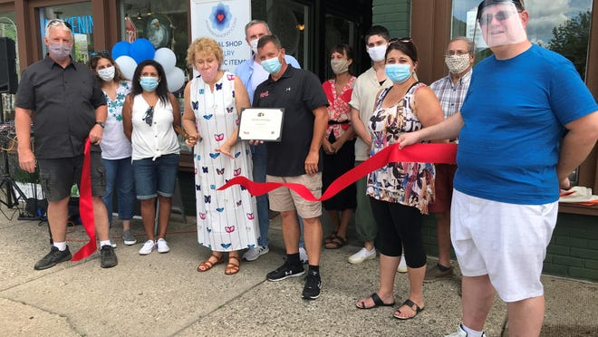 In front at the ribbon cutting are Councilman Tim Simmons, Councilwoman Maria Mann,Rosa Everett, owner Mariola Jedynasty, Mayor Kelly B. Decker, Councilwoman-at-Large LisaRandazzo and Councilman Regis Foster. Behind them are friends and family members.