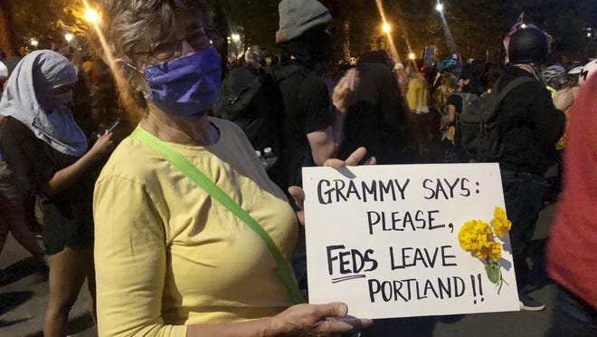 Mardy Widman, a 79-year-old grandmother of five, protests the presence of federal agents outside the Mark O. Hatfield Federal Courthouse in Portland, Ore., Monday, July 20, 2020. Widman said this was her first time protesting since George Floyd's death because the Trump administration's decision to send federal agents to Portland was more important than her fears of catching COVID-19.