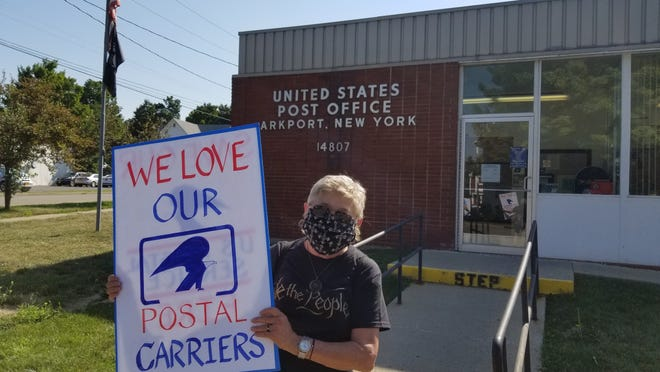 Lynn Sulyma of Hornell demonstrates in support of the US Postal Service outside of the Arkport post office Saturday. Sulyma, a veteran, blamed recent cuts to the USPS for a delay in receiving her cancer medication by mail this summer.