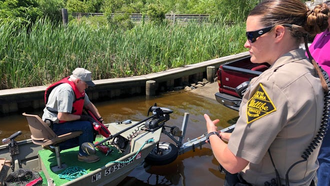 Barbara Smith, N.C. Wildlife law enforcement officer, checks with Doug Maxwell to make sure he has all required safety equipment aboard his boat on Wednesday. N.C. Wildlife is urging safe boating practices following 35 boating deaths in 2018.