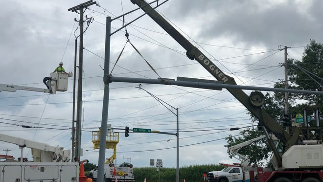 A Wooster City crew works to fix a damaged traffic signal arm hit by a dump truck Wednesday at the intersection of State Route 585 and Old Airport Road.