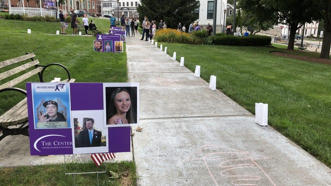 Luminaries and photos of overdose victims line the Newton Green during a vigil to mark International Overdose Awareness Day Monday, Aug. 31.