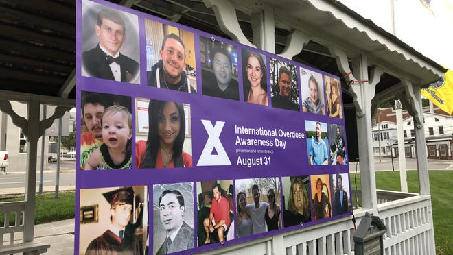 A banner with photos of community members lost to overdose hangs in a gazebo on the Newton Green during a vigil to mark International Overdose Awareness Day Monday, Aug. 31.