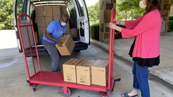 Sylvester Hampton of River Valley Regional Food Bank loads boxes of hand sanitizer as part of a donation made to Donald W. Reynolds Cancer Support House as Angie Clegg of the Cancer Support House looks on.