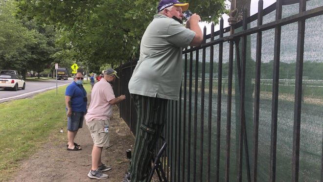 A fan uses a step-stool so he can see horse racing action above the fence in July at the Saratoga Race Course in Saratoga Springs.