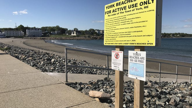 A bright yellow sign informs visitors of Short Sands Beach in York Beach, Maine, of the current restrictions in place amid the COVID-19 pandemic on May 31.