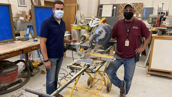 Mo Atilano, right, stands with Pueblo County pubic information officer Adam Uhernik in the county carpenter's shop. Atilano has designed and built about 20 plexiglass safety barriers for county buildings among other projects.