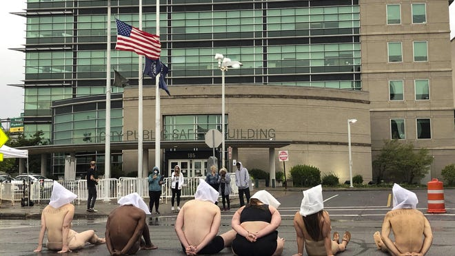 """Naked protesters, wearing """"spit hoods"""" in reference to the killing of Daniel Prude, demonstrate outside Rochester's Public Safety Building in Rochester, N.Y., Monday, Sept. 7, 2020."""