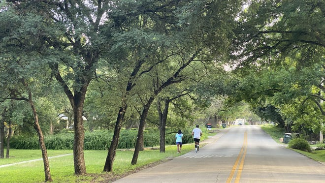A couple jogs along Reveille Road toward Bee Cave Road  in West Lake Hills on a June evening. Several residents have said drivers exceed the 25 mph speed limit on the narrow, half-mile stretch frequently used as a cut through, and have asked the city to install speed bumps.