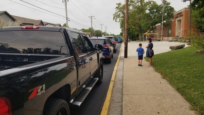 Cars line up Tuesday morning Jefferson Middle School for help with a technology fix as Columbia Public Schools started online.