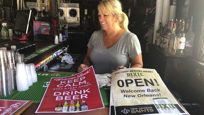 "In this June 12, 2020 photo, Cherie Boos, manager of Lafitte's Blacksmith Shop Bar on Bourbon Street, stands behind the bar as workers prepare it for reopening. The city is allowing bars to open â€"" with limited capacity and without live music â€"" on Saturday. Bars were among the businesses shut down in mid-March as coronavirus infections increased in New Orleans and Louisiana became a hot spot for the disease."