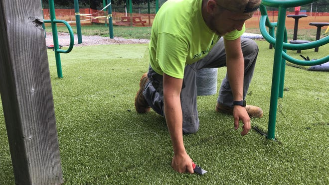 AJ Cianciolo, of ForeverLawn CTNY, lays down a new turf surface under Owen Bell Park's playscape area in Dayville on Friday.