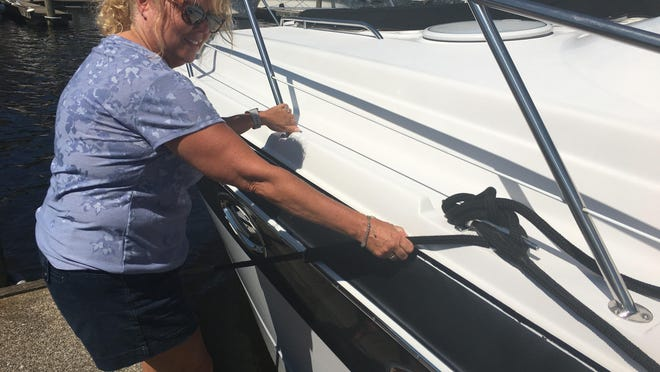 Cathryn Martyn of Windham ties off her boat at The Marina at American Warf in Norwich to prepare for Tropical Storm Isaias.