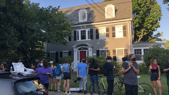 About 30 people gather outside the home of Gov. Gina Raimondo Saturday evening to urge her to divert funds from the Providence police.
