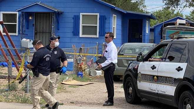 Pueblo Police Det. Jonathan McCluskey, right, and other members of the police department investigate a double homicide on the 1400 block of East 18th Street.