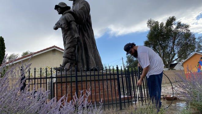 Robert Bennett helps clean the statue of Martin Luther King Jr. and Emmett Till on Thursday afternoon.